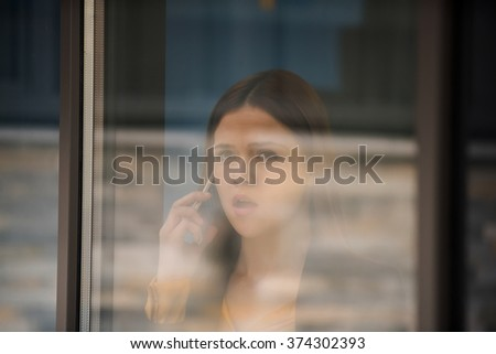 business woman in modern glass interior speak on mobile - stock photo