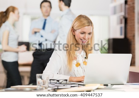 Business woman in office using laptop. Portrait of busy secretary typing on keyboard. Portrait of happy smiling young businesswoman working on laptop with her colleagues in background. - stock photo