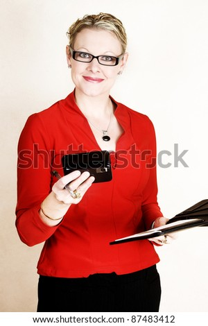 Business woman in red suit holding an open folder and cell phone - stock photo