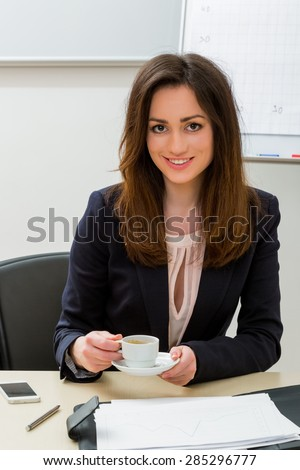 Business woman in the office. Secretary drinking coffee in the workplace. - stock photo