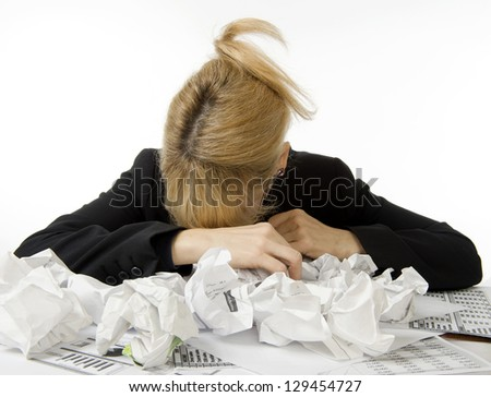 Business woman is dismayed with her head down in pile of paperwork - stock photo