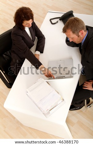 business woman is showing something in the computer to the business man compared to her - stock photo