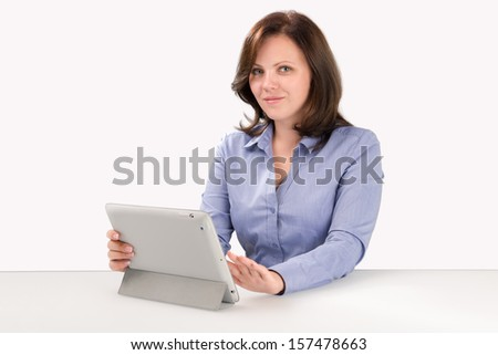 Business woman is working with tablet computer and looking at the camera, business concept - stock photo