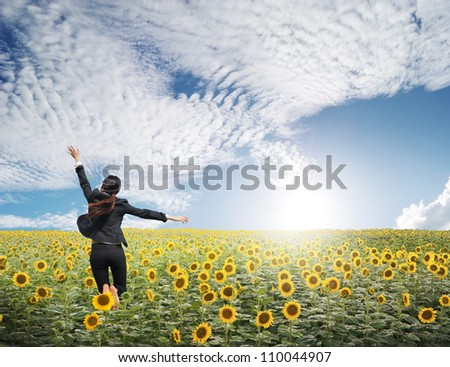 Business woman jumping in  blue sky over sunflowers field - stock photo