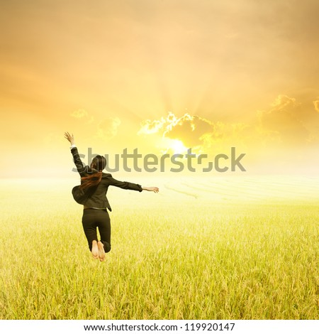 Business woman jumping in Yellow Rice fields and sunset - stock photo