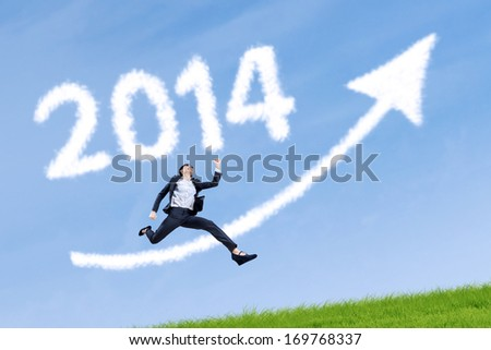 Business woman jumping over arrow sign with 2014 on the grass - stock photo