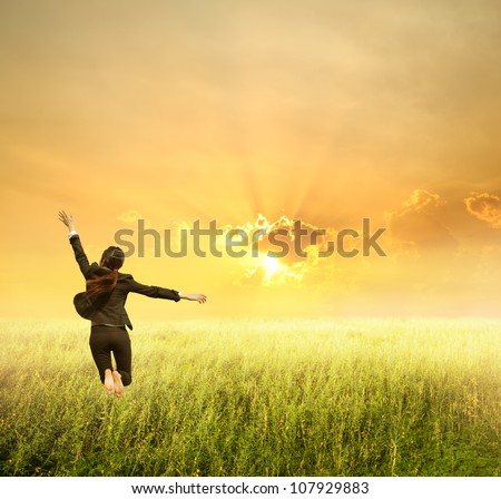 Business woman jumping to sunset in grassland - stock photo