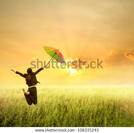 Business woman jumping to sunset in grassland with rainbow umbrella - stock photo