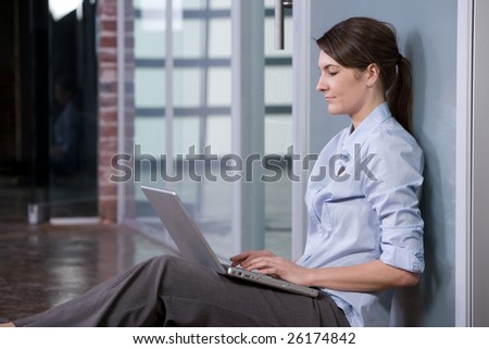 Business woman laptop in modern lobby - stock photo