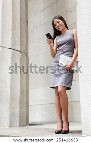 Business woman lawyer using apps on smartphone outside to read news or text sms. Successful young multiracial Caucasian / Asian Chinese professional woman standing in suit dress holding newspapers. - stock photo