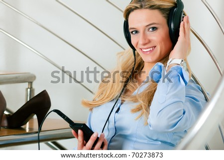Business woman listening music at home sitting relaxed on the stairs - stock photo