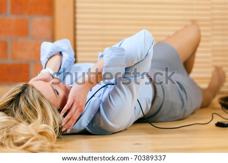 Business woman listening music or a language course at home lying relaxed on the floor - stock photo
