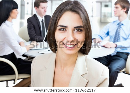 Business woman looking at camera with a smile - stock photo