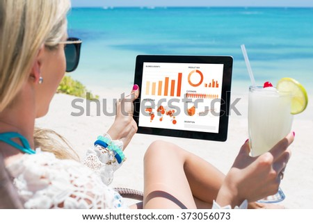 Business woman looking at graphs and charts on digital tablet - stock photo