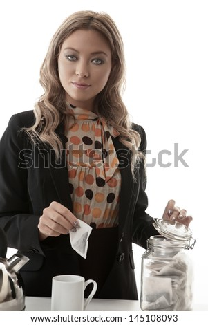 business woman making tea at the office on her break - stock photo