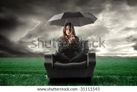 business woman on an armchair lost in countryside during a storm - stock photo