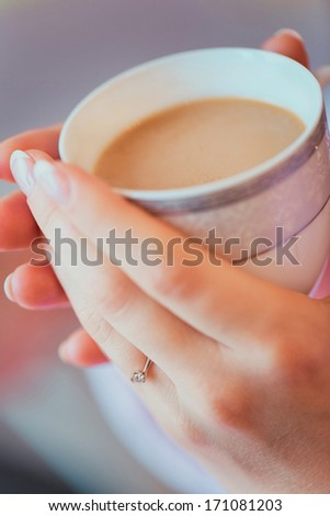 Business woman on coffee breaks. Making primary job came the sweet moment when you can drink a warming coffee with milk, to look out the window and admire the pleasant day. - stock photo