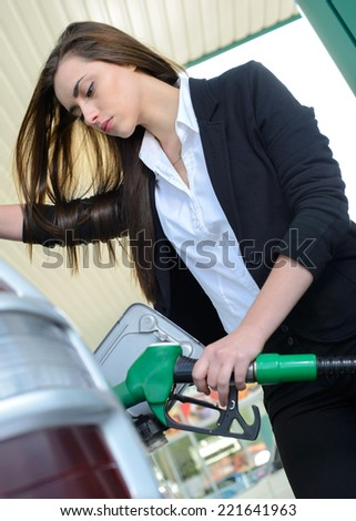 Business woman on filling station, while filling your car - stock photo