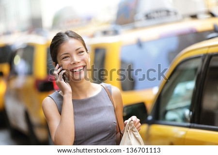 Business woman on smart phone in New York City, Manhattan walking in dress suit holding doggy bag smiling and laughing, Young multiracial Asian Caucasian professional female businesswoman in her 20s. - stock photo