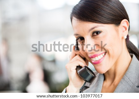 Business woman on the phone taking a call and smiling - stock photo