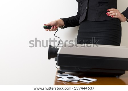 Business woman operating a slide projector against a white wall - stock photo