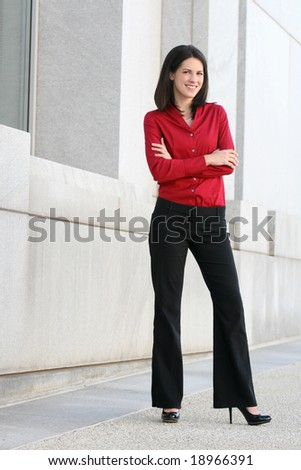 Business woman outdoors talking on cell phone, street view in front of a corporate office building - stock photo