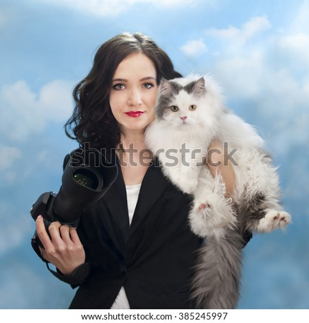 Business woman photographer and her cat on a background of the spring sky - stock photo