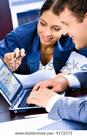 Business woman pointing at laptop and explaining a plan of work to colleague - stock photo