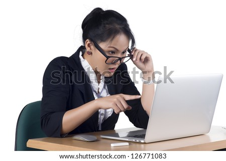 Business woman pointing at laptop's screen looking shocked and surprised, Isolated white background. Model is Asian woman. - stock photo