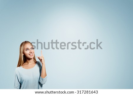 Business woman pointing showing and looking to the side up at empty copyspace. Caucasian female businesswoman standing isolated on blue background in half body length. - stock photo