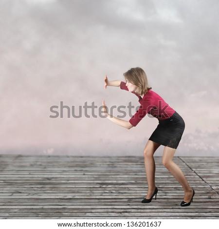 Business woman pushing something imaginary - stock photo