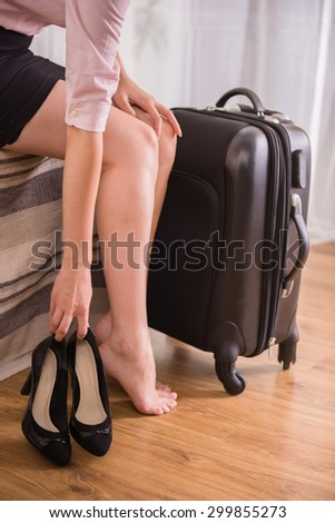 Business woman putting down her shoes while sitting on bed near suitcase at the hotel room. Close-up. - stock photo