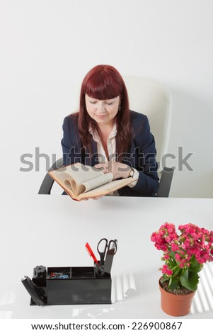 business woman reads book in a comfortable modern office - stock photo