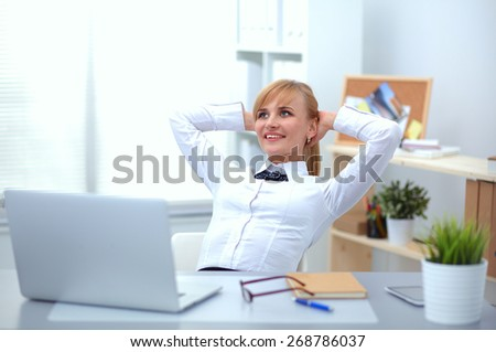 Business woman relaxing with  hands behind her head and sitting on a chair - stock photo
