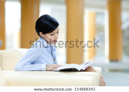 Business woman rests at the sofa reading professional literature - stock photo
