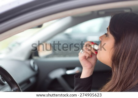 Business woman retouching her makeup while stopped in the traffic - stock photo