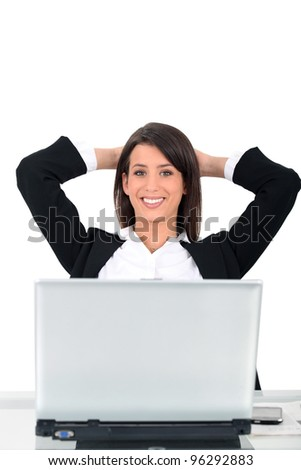Business woman sat at desk in front of computer - stock photo