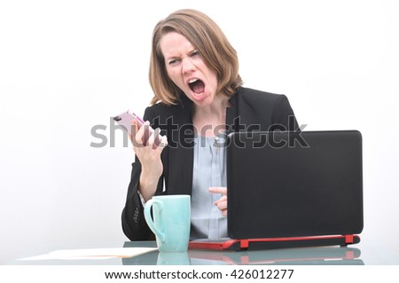 Business woman screaming into phone while at desk  - stock photo