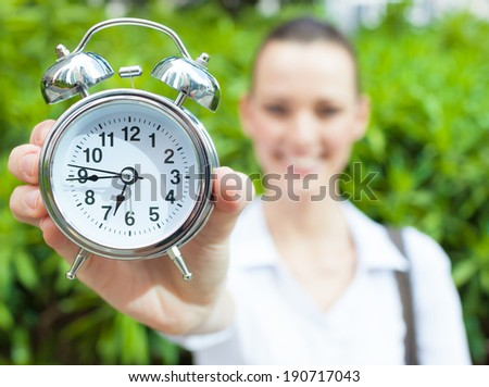 Business woman showing a clock to the camera.  - stock photo