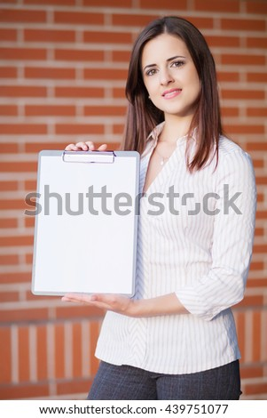 Business woman showing blank clipboard at her office  - stock photo