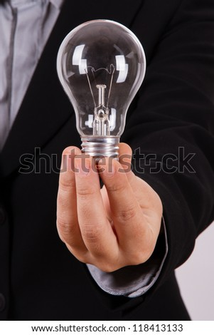 Business woman shows and holds lightbulb. - stock photo