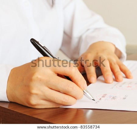 Business woman signing a contract in Mandarin, Chinese - stock photo