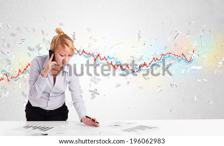 Business woman sitting at table with stock market graph 3d letters  - stock photo