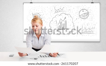 Business woman sitting at white table with hand drawn graph charts - stock photo