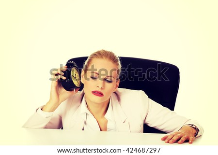 Business woman sitting behind the desk and listen to alarm clock - stock photo