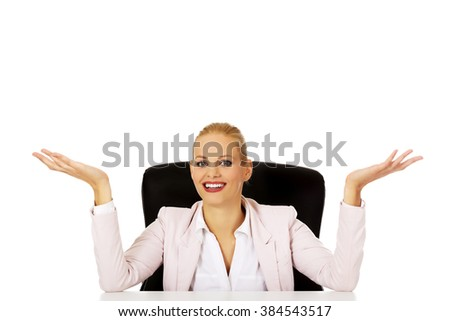 Business woman sitting behind the desk and making don't know sing - stock photo