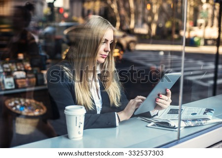 Business woman sitting in cafe and using tablet pc and drinking coffee - stock photo