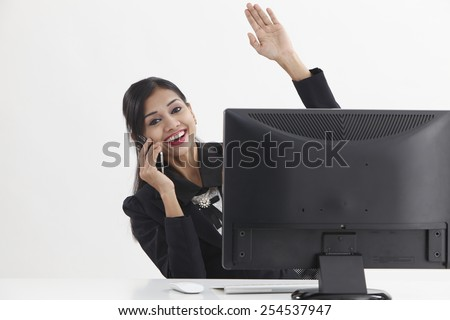 business woman sitting in front of computer,talking and waving to camera - stock photo