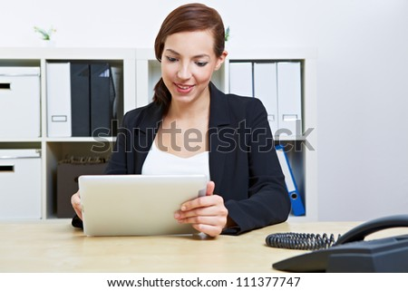Business woman sitting in her office using a tablet computer - stock photo