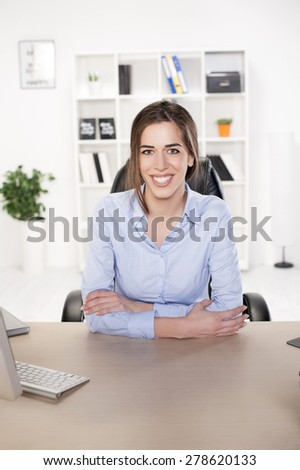 Business woman sitting in office looking at the camera and smiling - stock photo